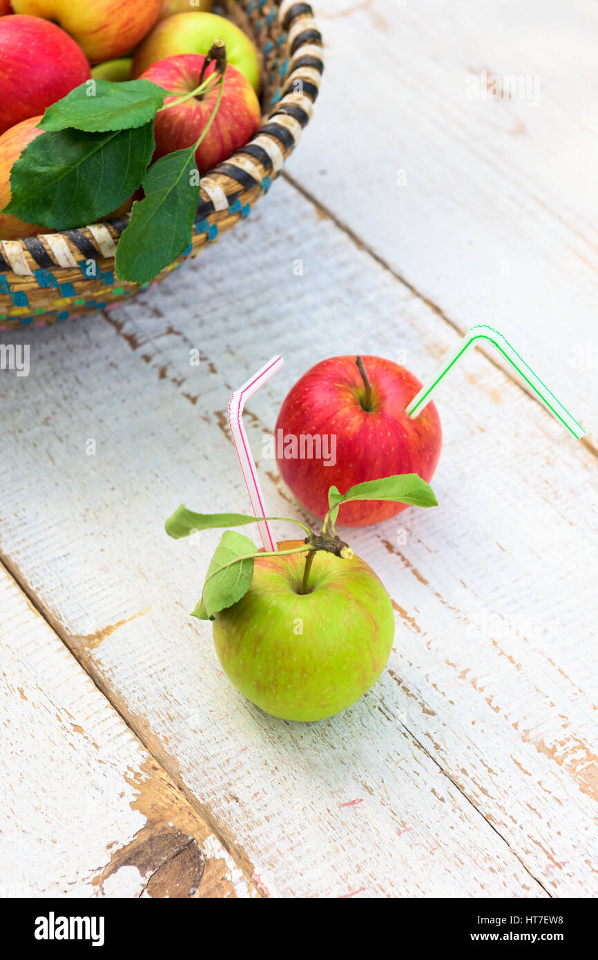 Organic apples in basket, on white vintage wooden background, healthy lifestyle concept - Stock Image