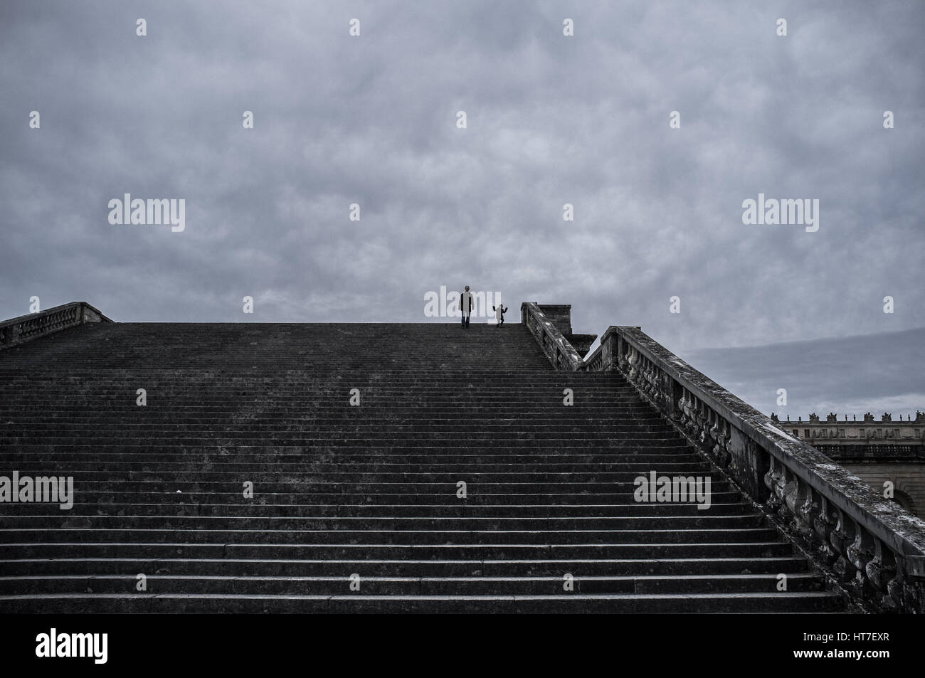 Father and son marching down the ladder hand in hand Stock Photo