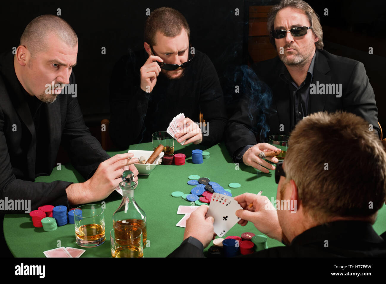 Photo of three male poker players staring across in anger at the fourth player. Cards have been altered to be generic. - Stock Image