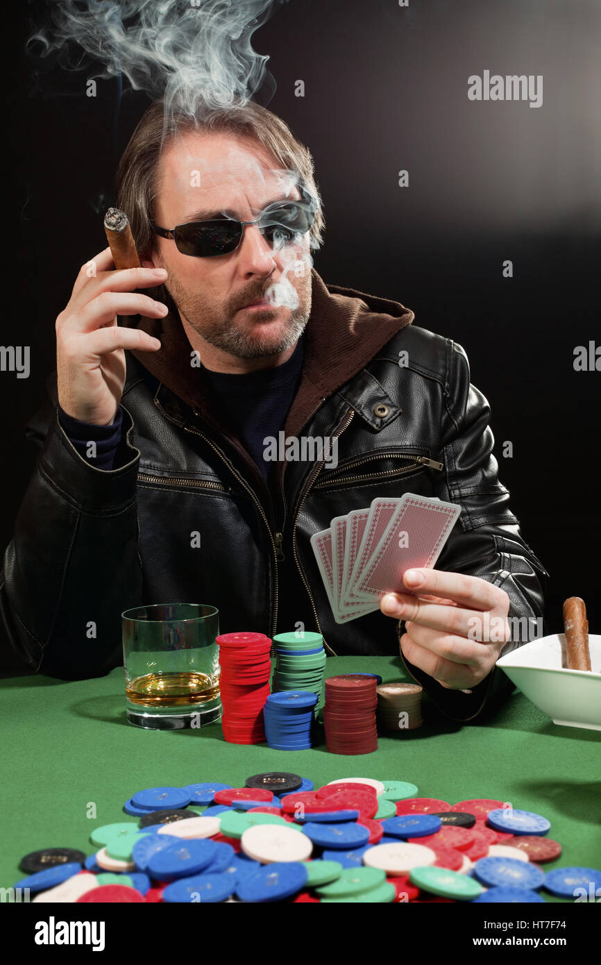 Photo of a man playing poker and smoking a cigar. Playing cards have been altered to be generic. - Stock Image