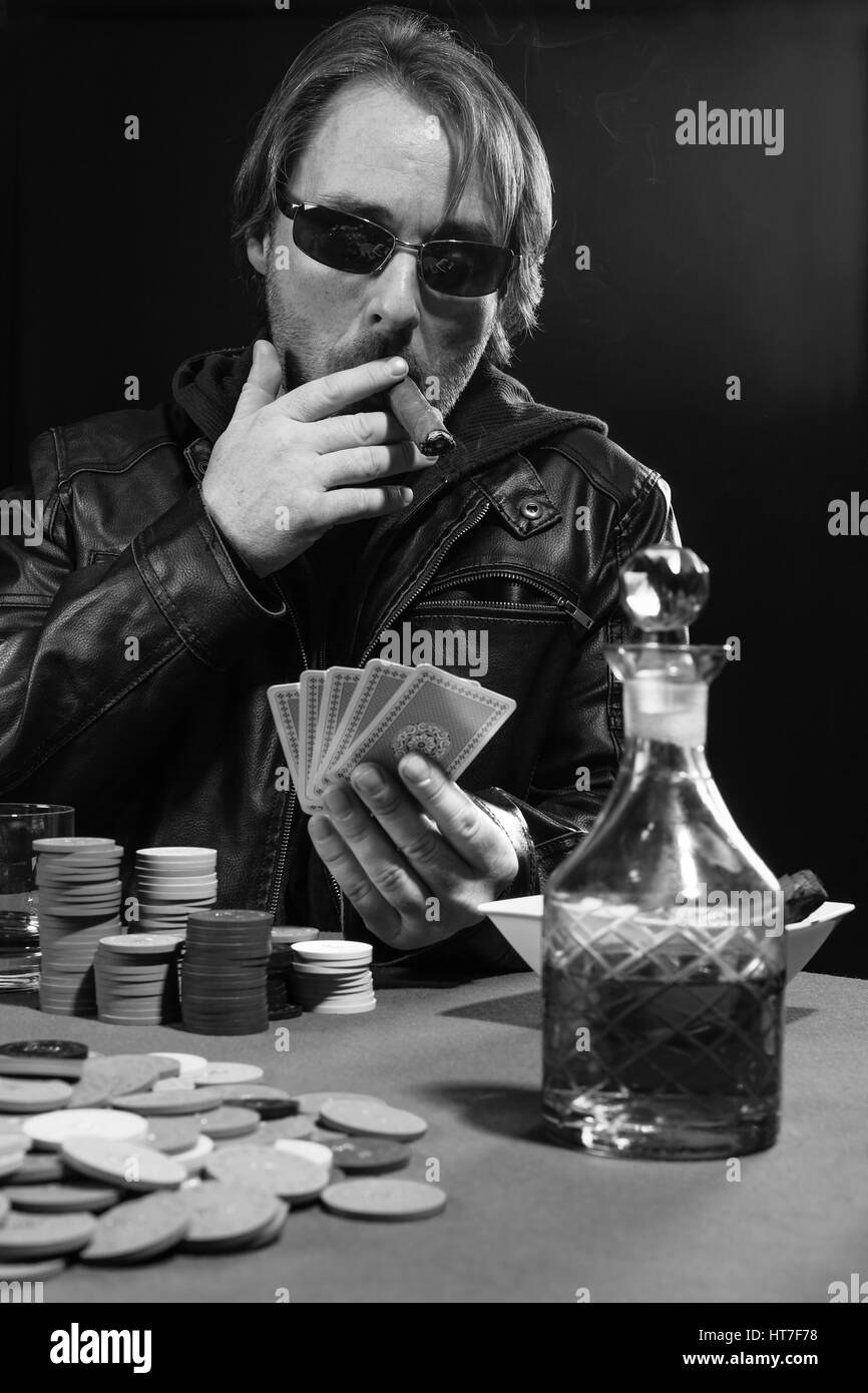 Photo of a man playing poker while wearing sunglasses and smoking a cigar. - Stock Image