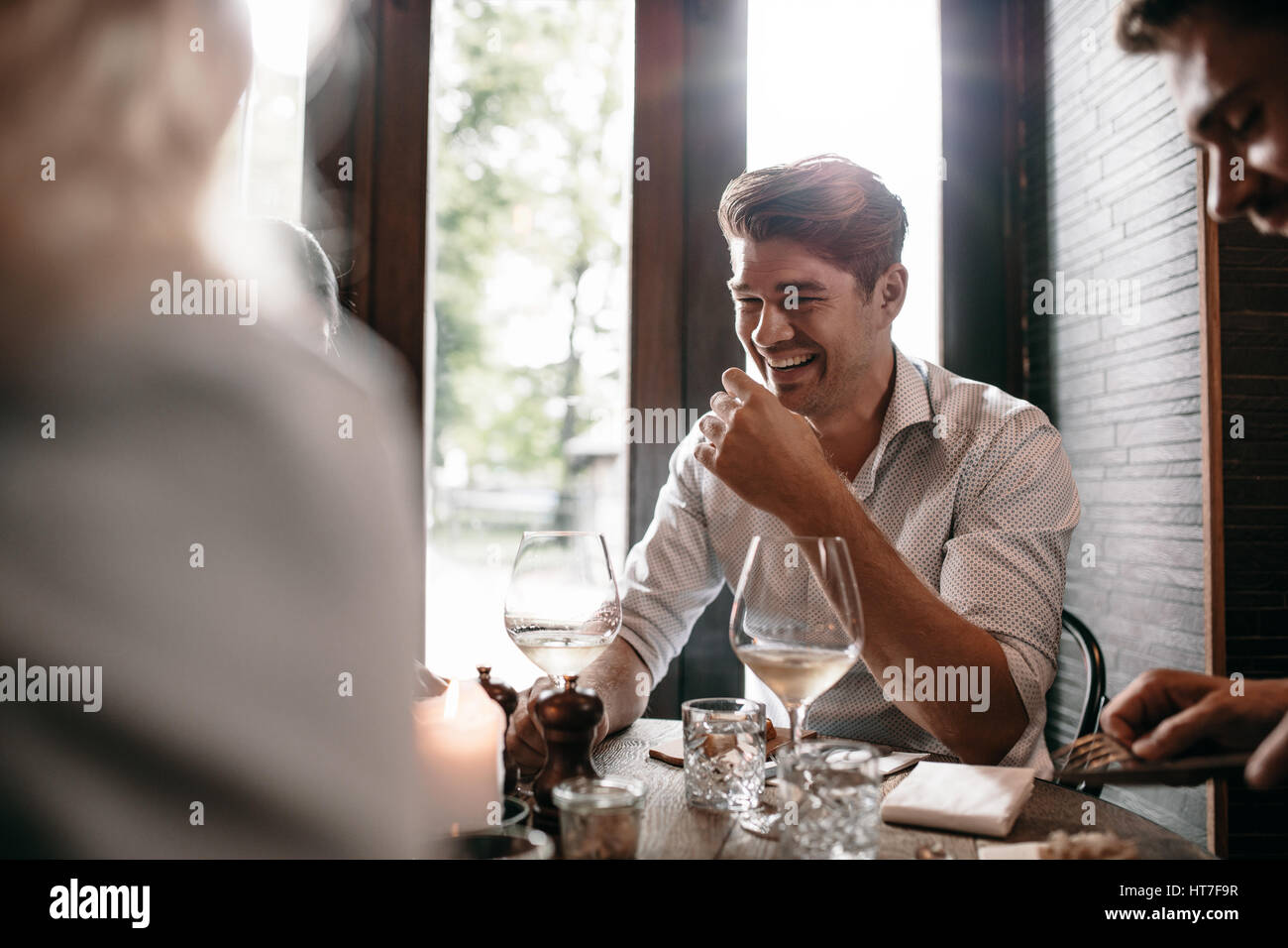 Indoor shot of young man smiling with friends at restaurant. Young people meeting at a cafe. Stock Photo