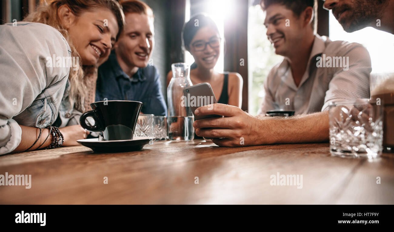 Horizontal shot of young friends watching photos on mobile phone. Group of young people sitting at cafe table and - Stock Image