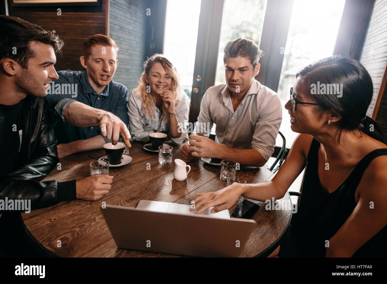 Group of young friends sitting at cafe with laptop and discussing. Young men and women looking at laptop at coffee - Stock Image