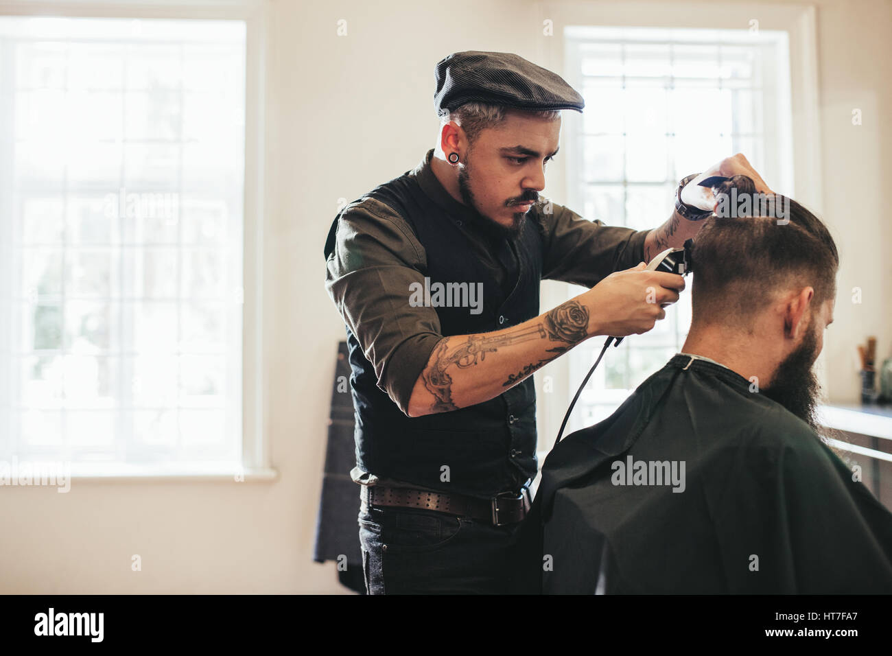 Hairstylist cutting hair of customer at barber shop. Man getting haircut at salon. - Stock Image
