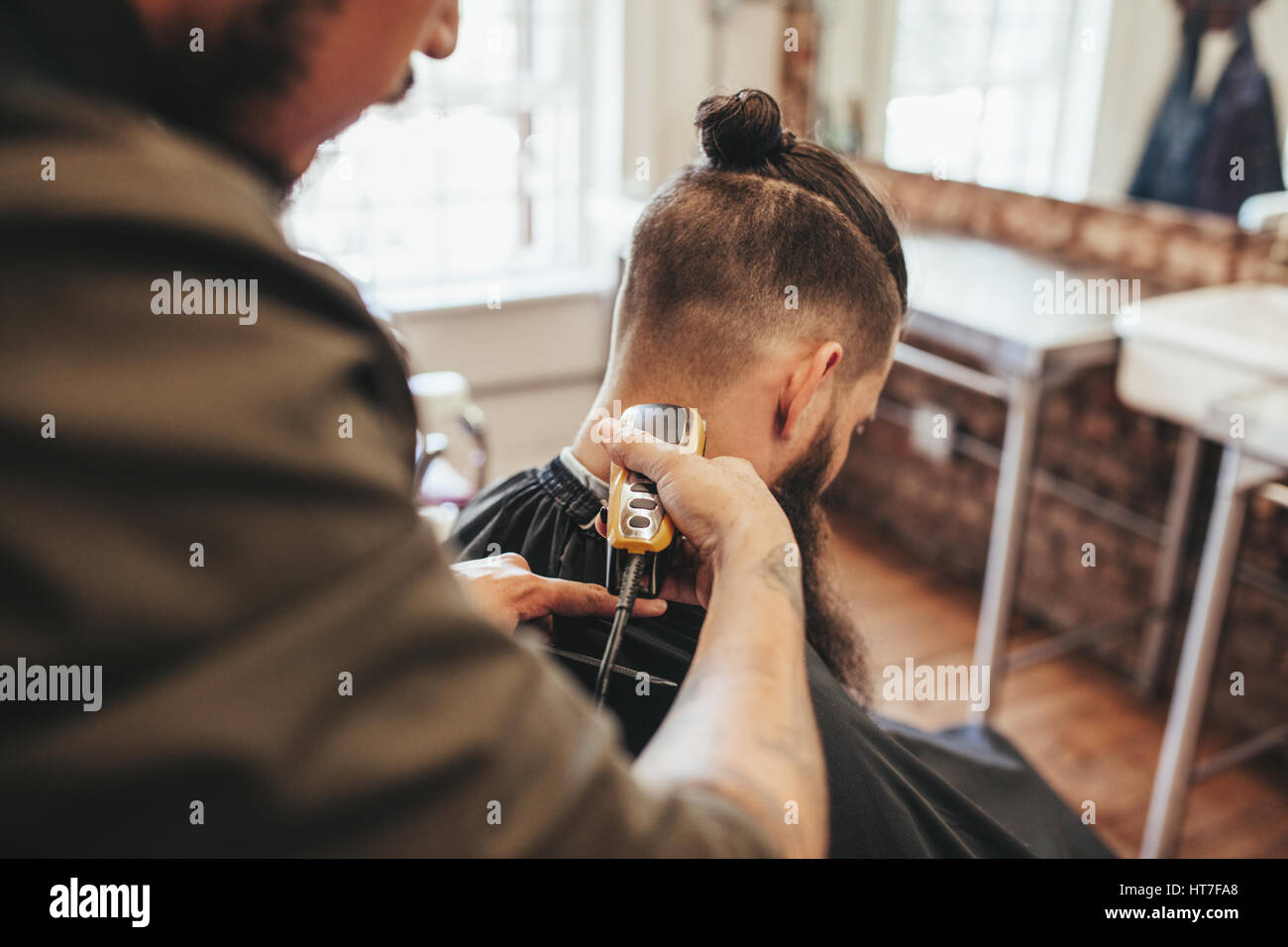 Man getting haircut by barber at salon. Hairdresser cutting hair of client with hair trimmer machine. - Stock Image