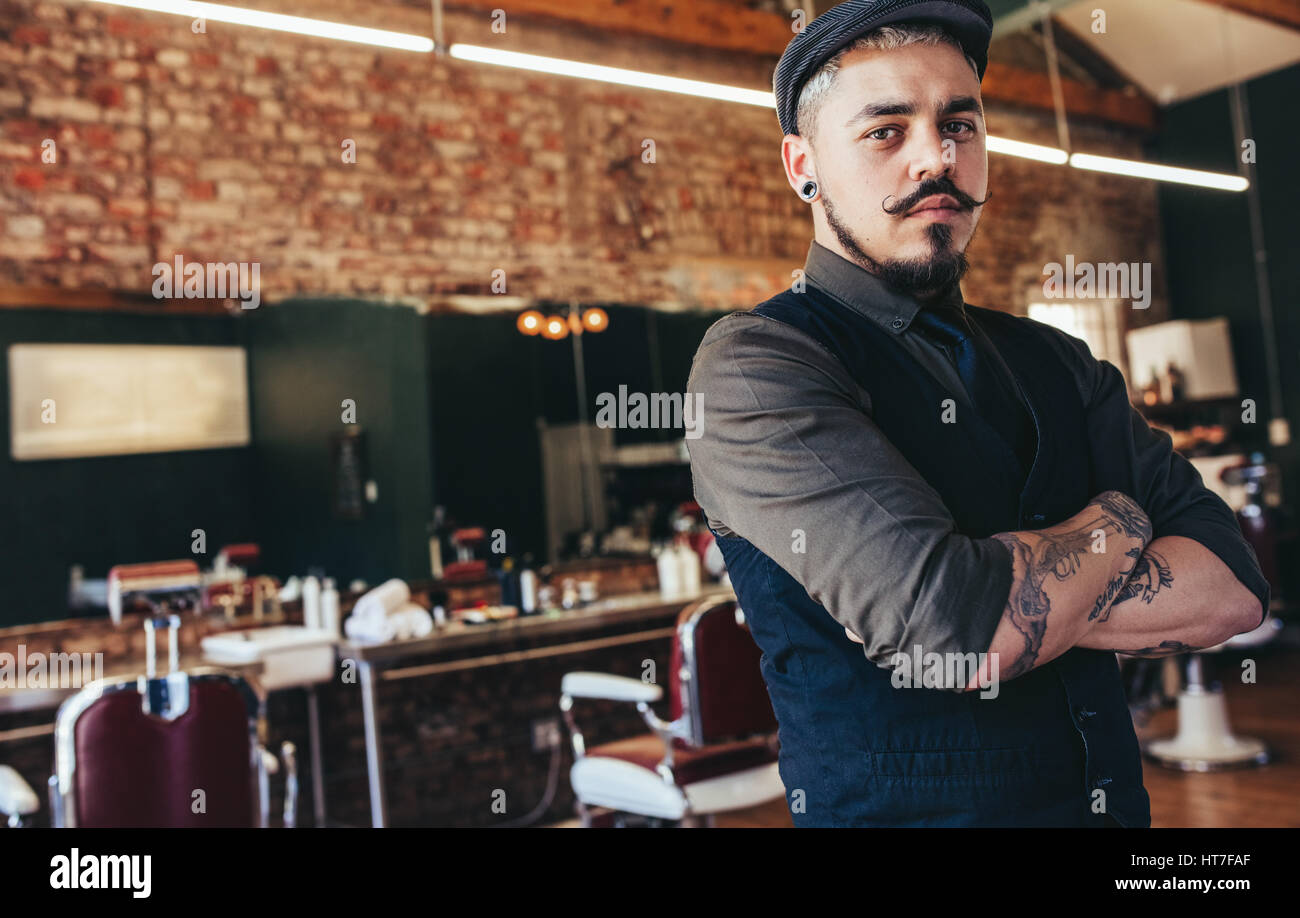 Portrait of young man standing with his arms crossed at barber shop. Stylish hairdresser in his salon looking at Stock Photo