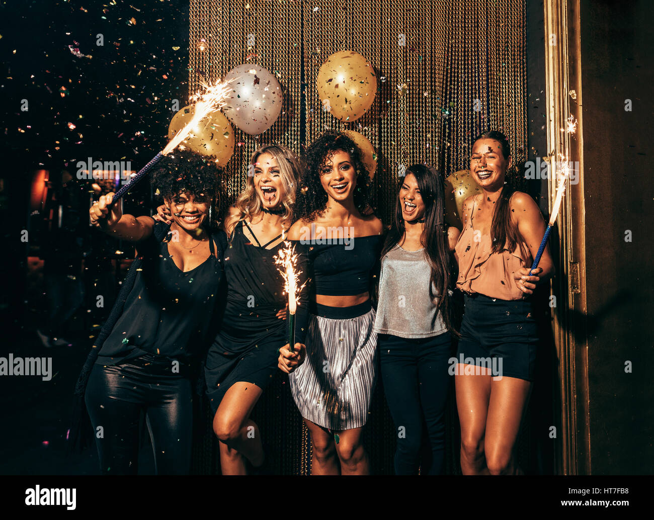 Shot of group of young women celebrating new years eve at the pub. Group of female friends with sparklers partying - Stock Image