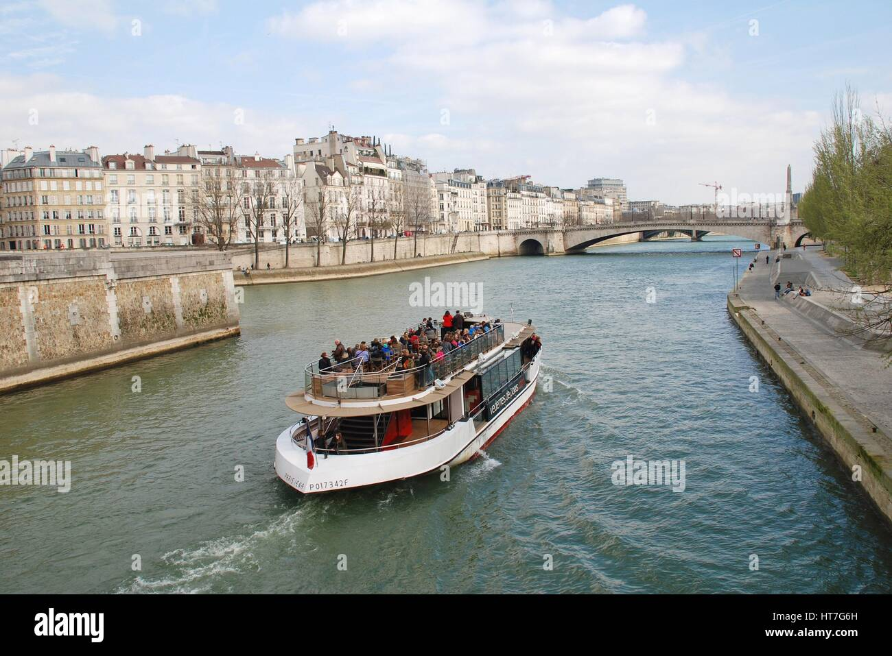 A pleasure boat cruises towards the Pont Saint Michel on the River Seine in Paris, France. Many sightseeing trips - Stock Image