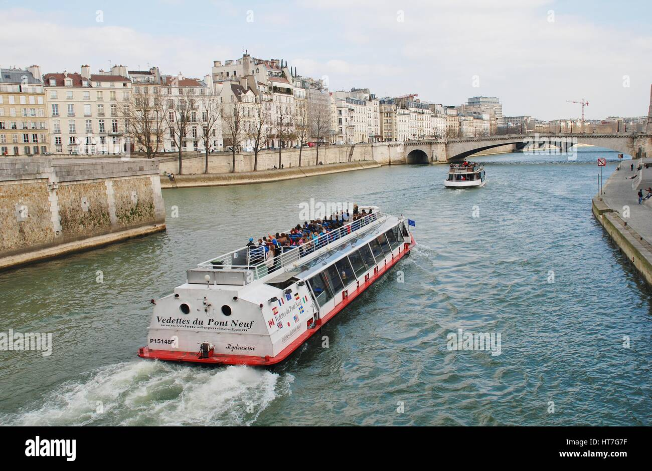 A pleasure boat cruises towards the Pont Saint Michel on the River Seine in Paris, France. Many sightseeing trips Stock Photo