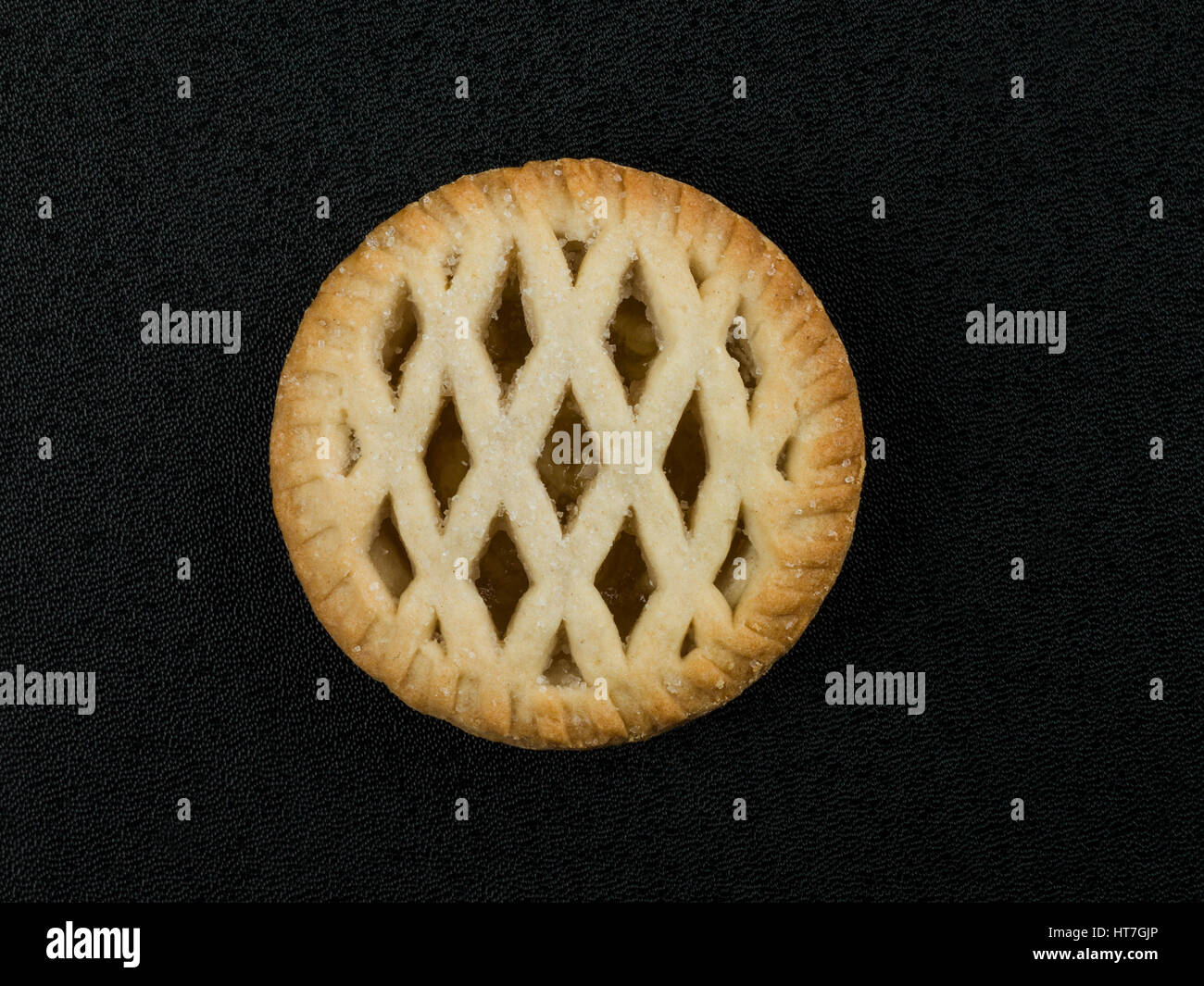 Lattice Topped Individual Bramley Apple Pie on a Black Background - Stock Image