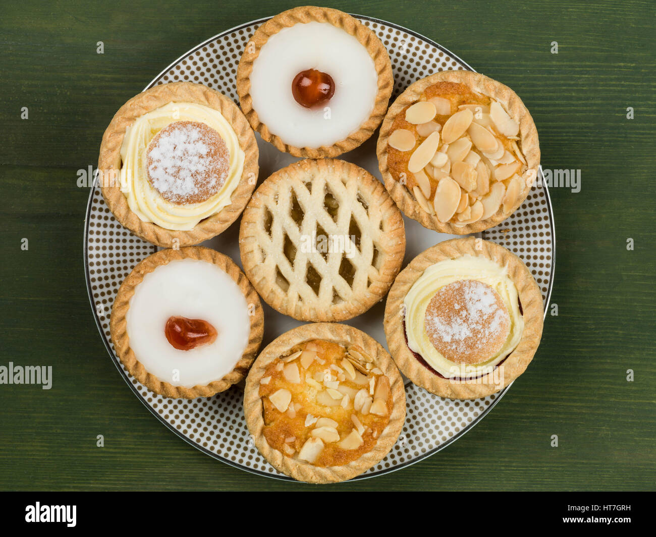 Plate of Assorted Individual Cakes or Tarts Against a Green Background - Stock Image