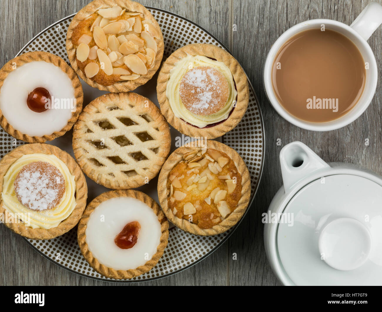 Plate of Assorted Individual Dessert Cakes or Tarts With a Pot of Tea - Stock Image