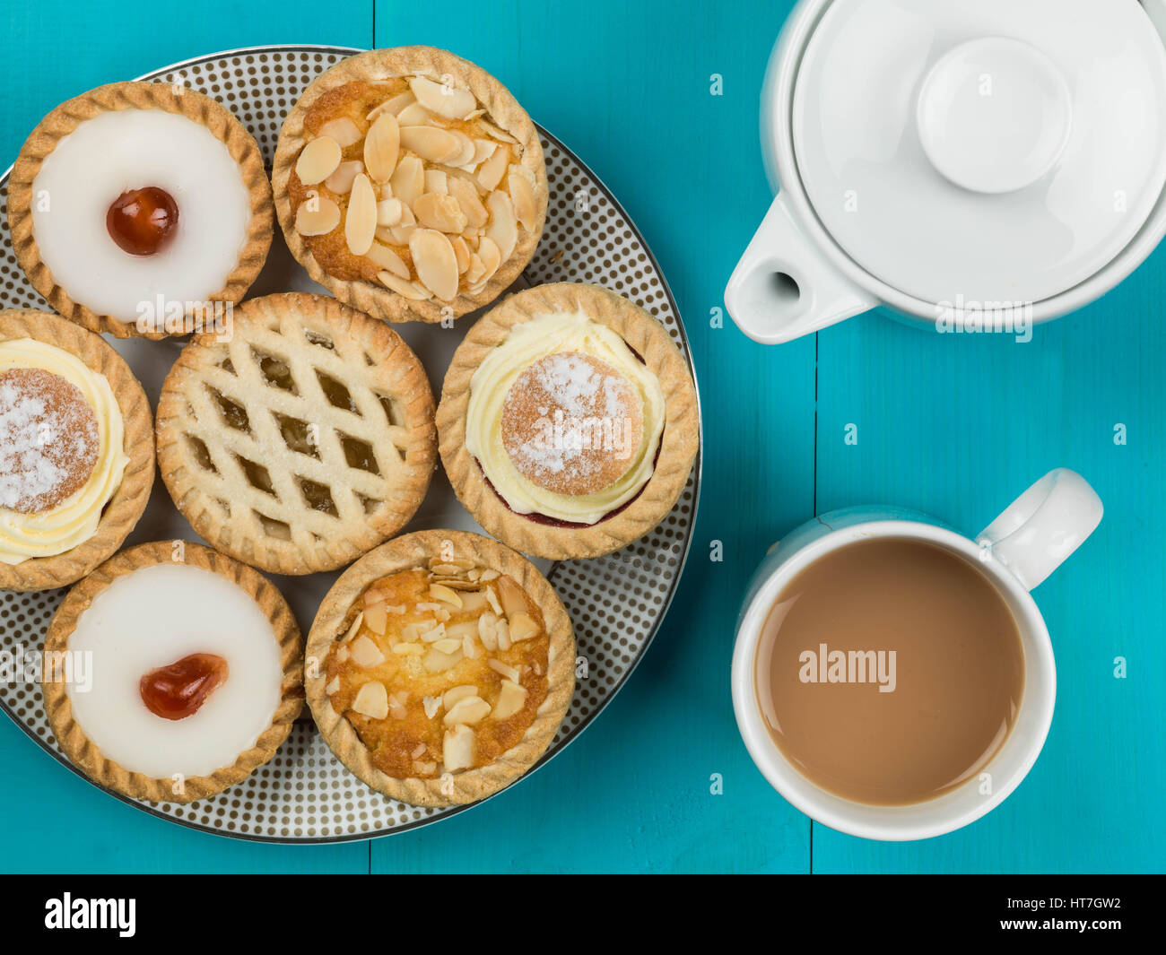 Plate of Assorted Individual Cakes or Tarts With a Pot of Tea Against a Blue Background - Stock Image
