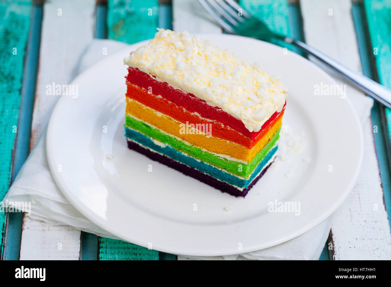Rainbow Cake On A White Plate Wooden Background Stock Photo