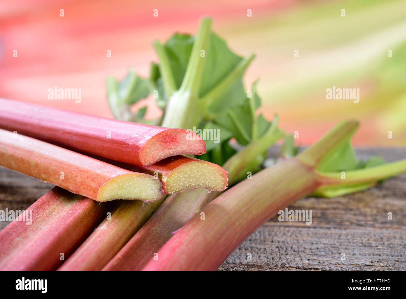 Fresh unpeeled rhubarb on a wooden table, in the background other rhubarb stalks in soft focus - Stock Image