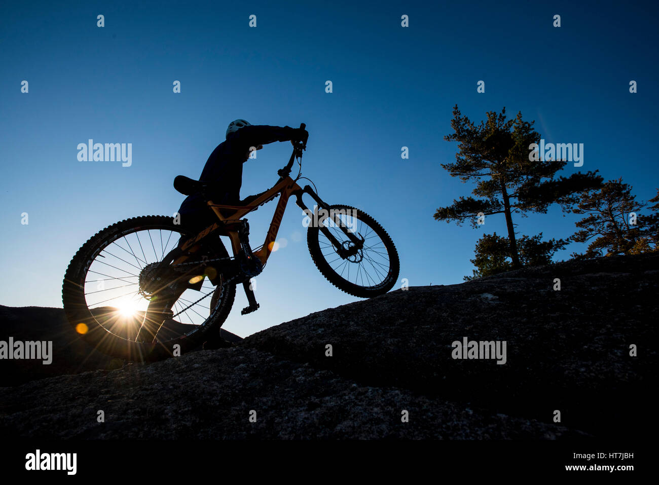 Silhouette Of Alex Leich With Mountain Bike On The Bare Granite Slabs In North Conway, New Hampshire - Stock Image