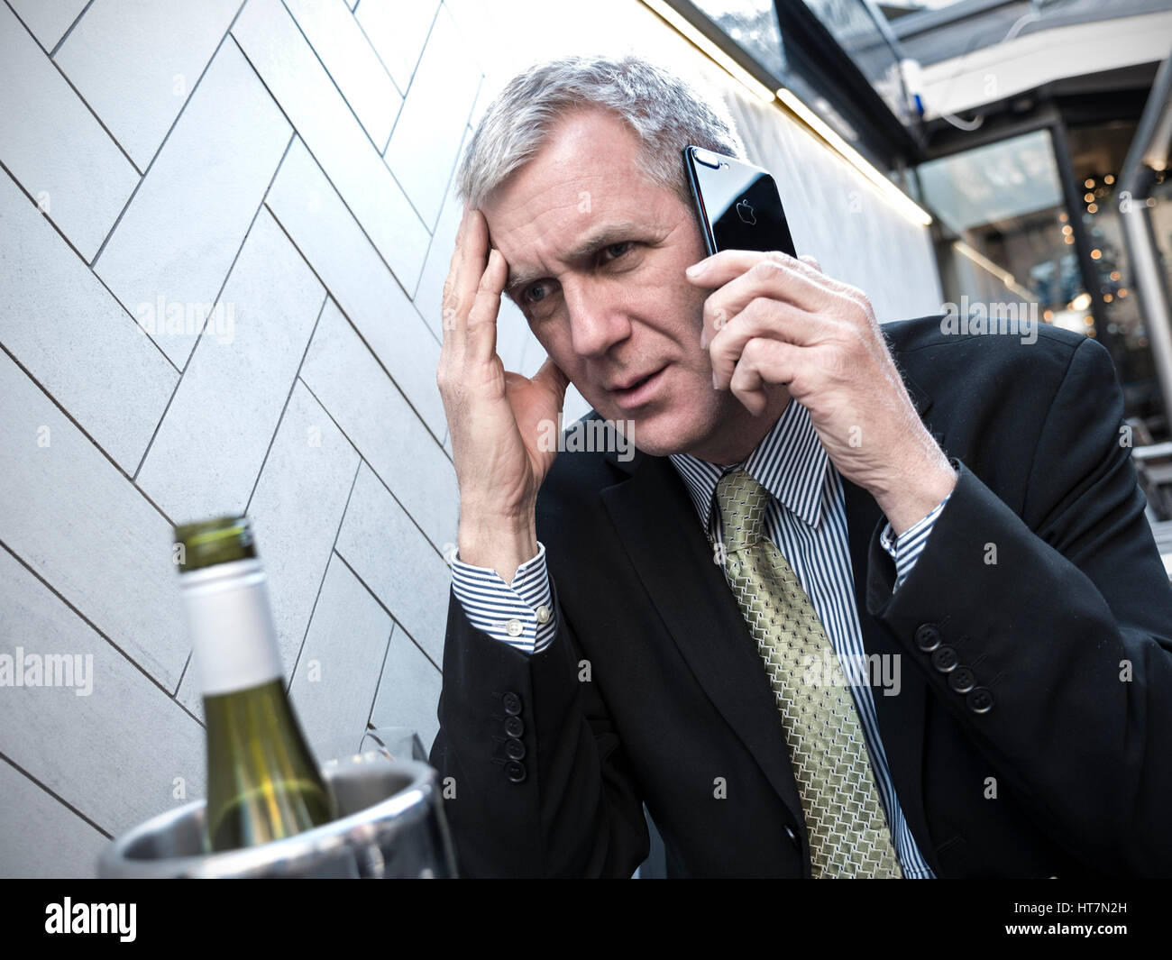 Mature city executive businessman, stressed and worried on his iPhone 7 plus smartphone at alfresco restaurant table - Stock Image