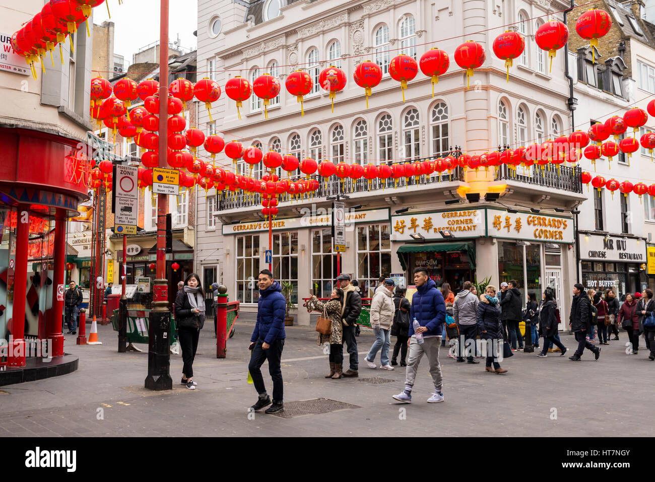 Tourists in Wardour street decorated with Chinese lanterns for the Chinese New Year celebrations. Chinatown, London, - Stock Image