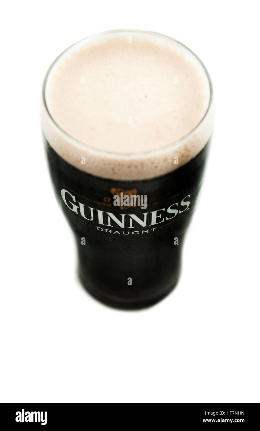 A Pint of Guinness Irish Stout with black body and creamy white head in a traditional pint glass taken from above - Stock Image