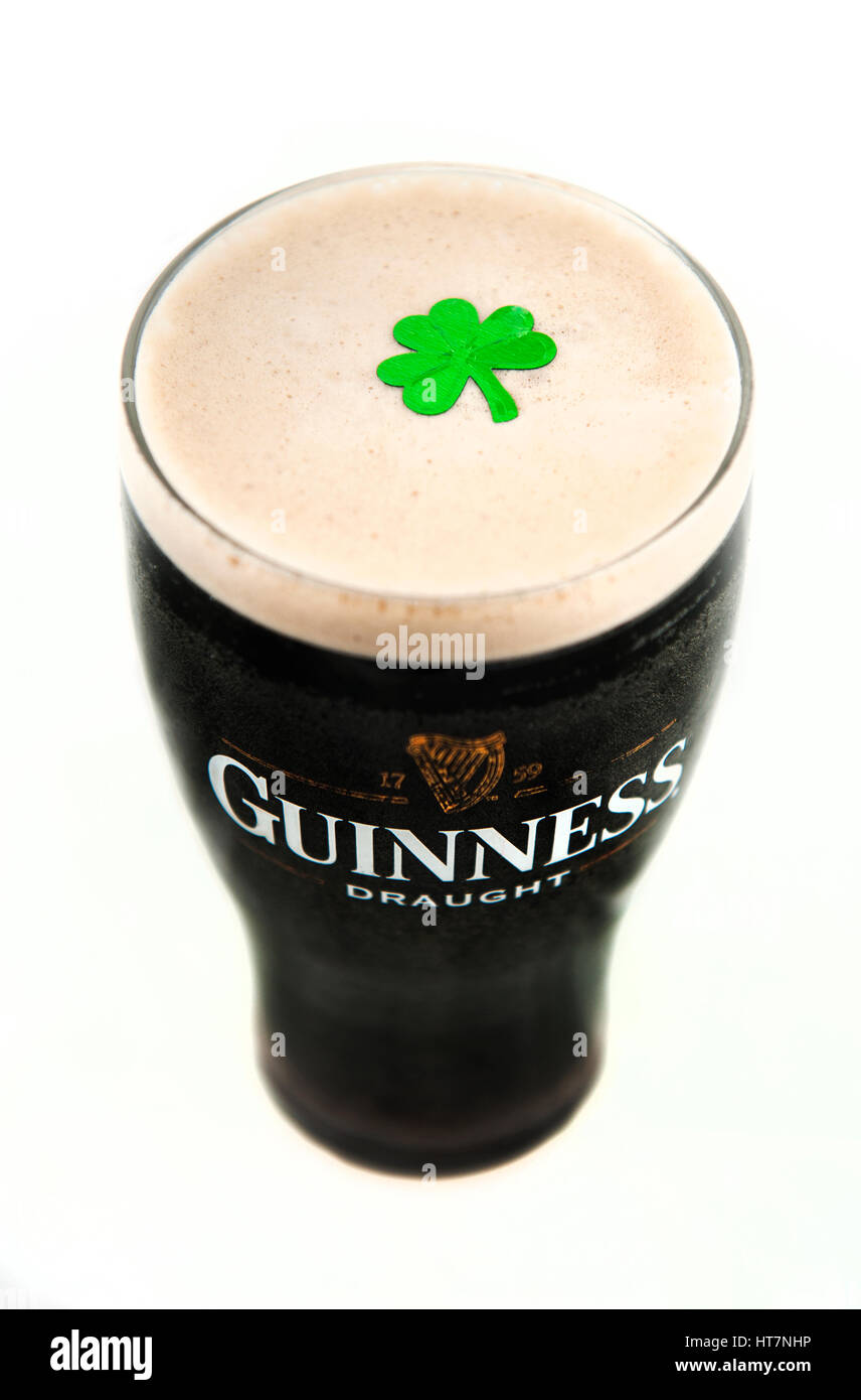 A distinctive black and cream pint glass of Guinness Irish Stout taken from above with a green confetti shamrock - Stock Image