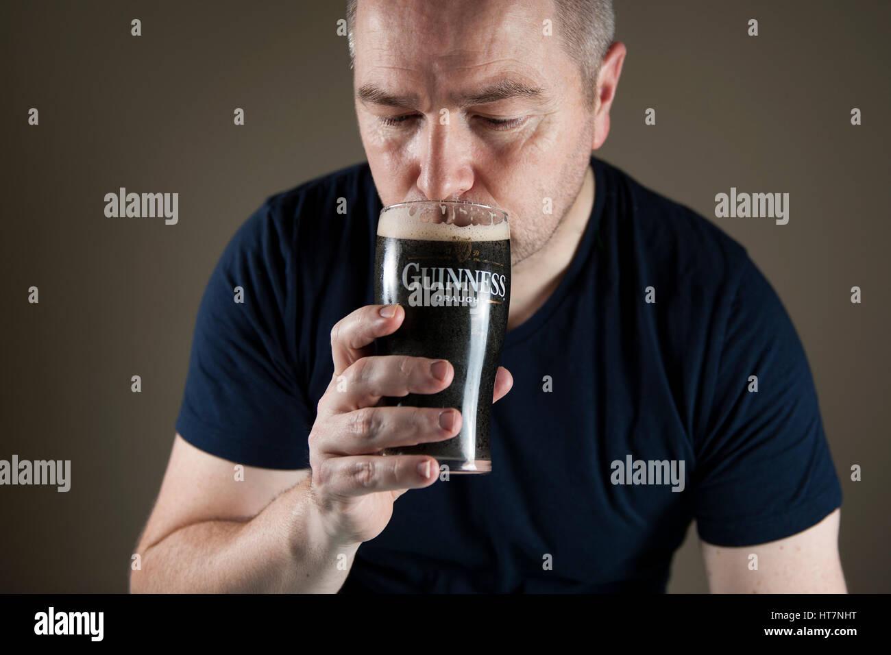 A closeup crop of a man drinking a pint of Irish Guinness stout - Stock Image