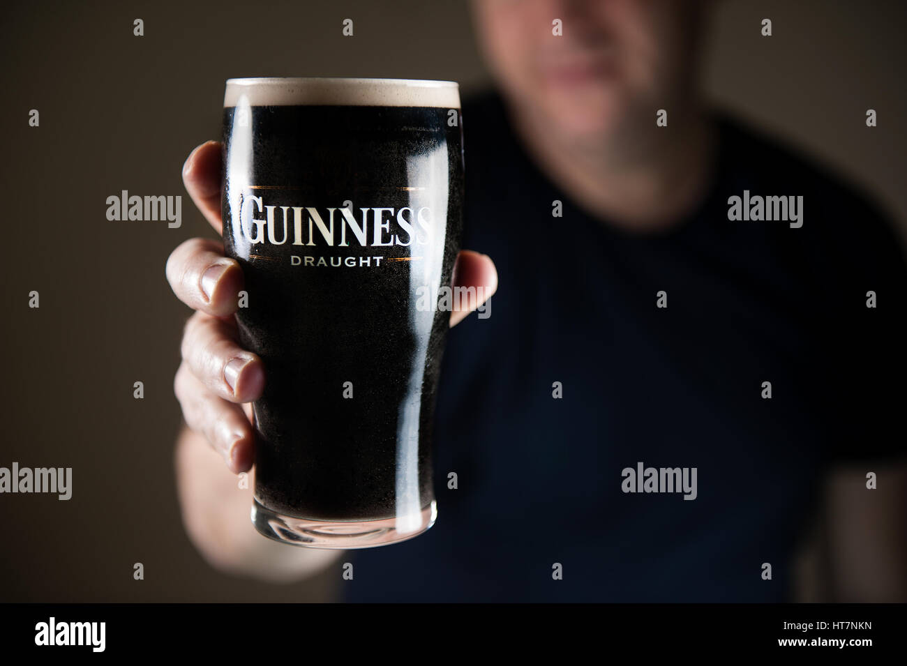 A smiling man in the background out of focus holding a traditional pint of Guinness Irish stout towards the camera - Stock Image