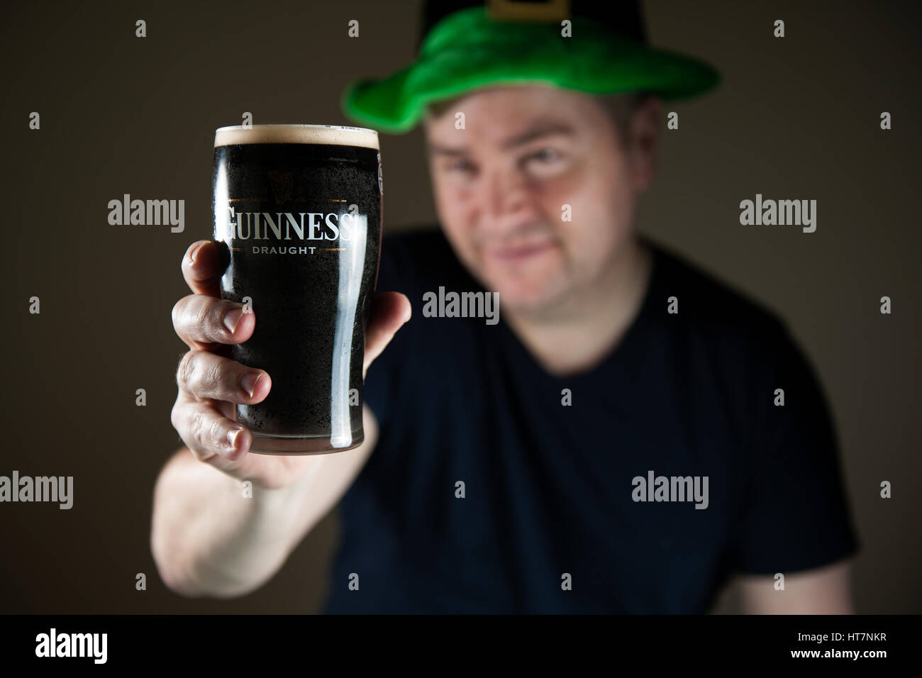 A man wearing a leprechaun hat on Saint Patrick's Day holding a pint of Guinness stout towards the camera - Stock Image