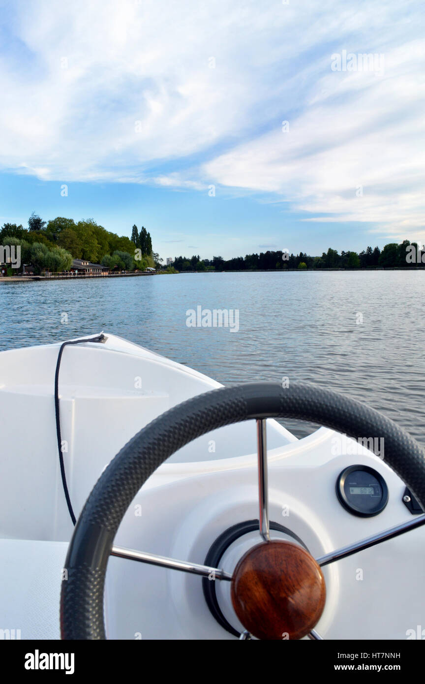 Navigation on board an electric boat on a lake. - Stock Image