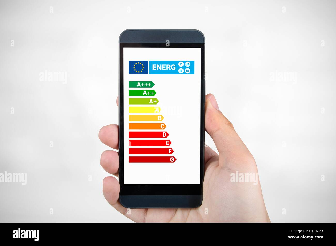 Man holding smartphone with energy efficiency chart. Savings in home concept - Stock Image