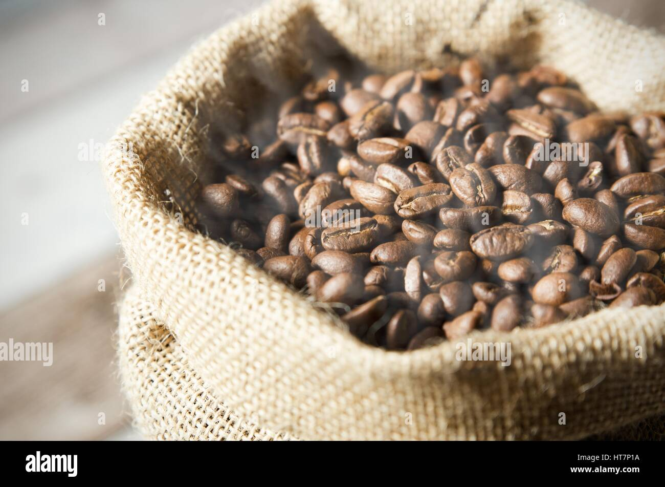 Close up coffee beans in jute bag on wooden table - Stock Image