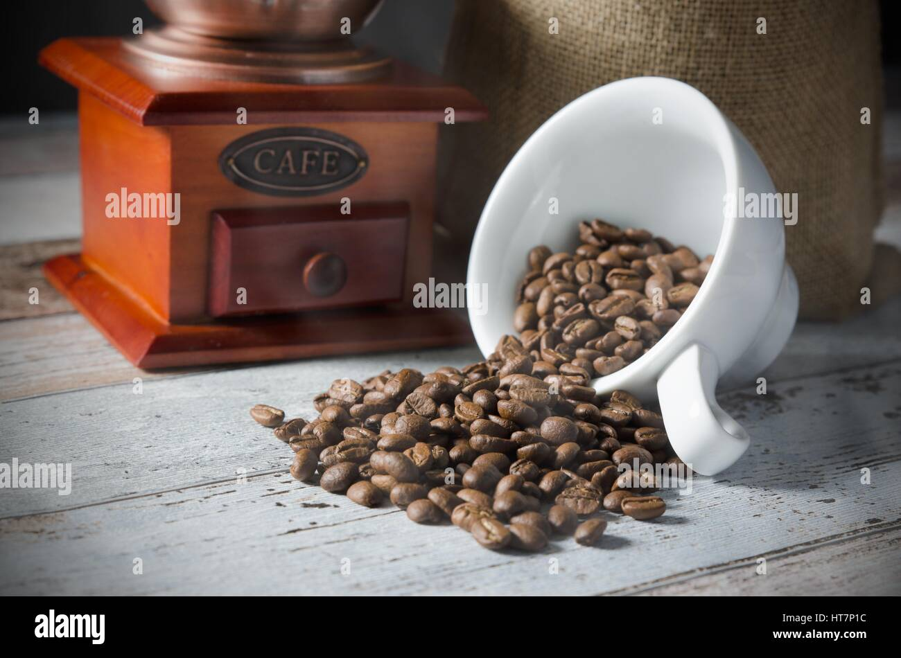Coffee grain spill from a cup. Jute bag of roasted beans and mill in background - Stock Image