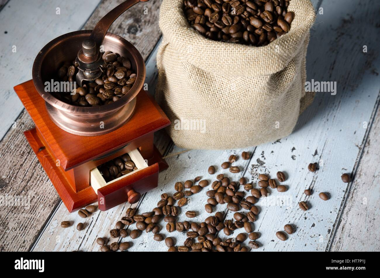 Coffee grinder with roasted beans. Vintage mill composition - Stock Image