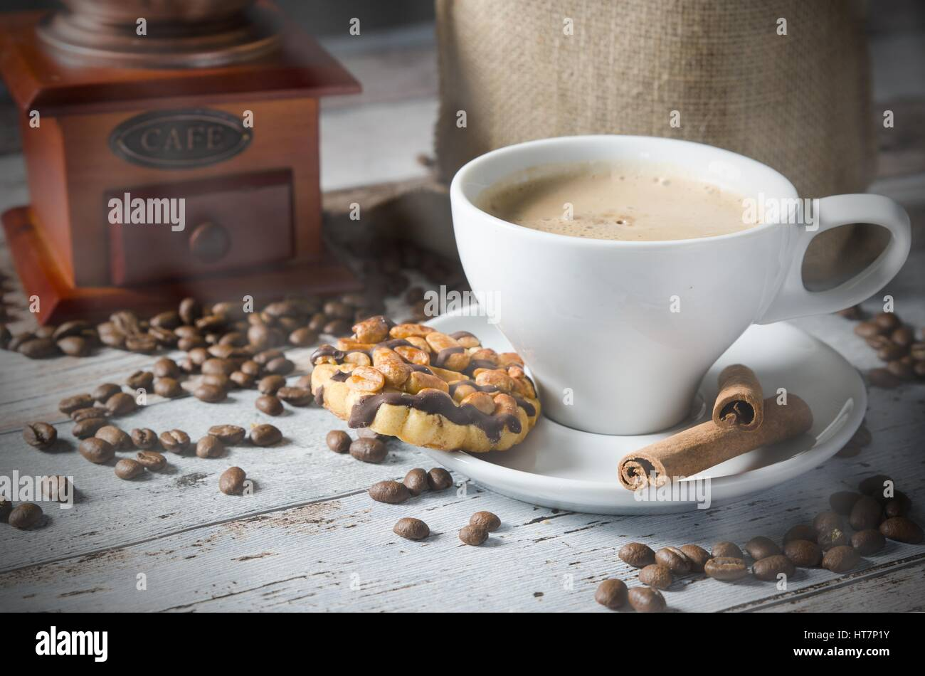 Coffee, roasted beans, mill grinder and cookie with nuts on wooden background - Stock Image