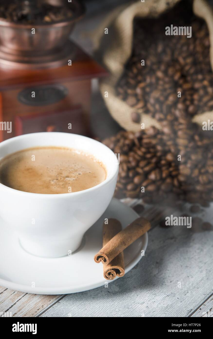 Coffee, roasted beans, mill grinder and cinnamon on wooden background Stock Photo