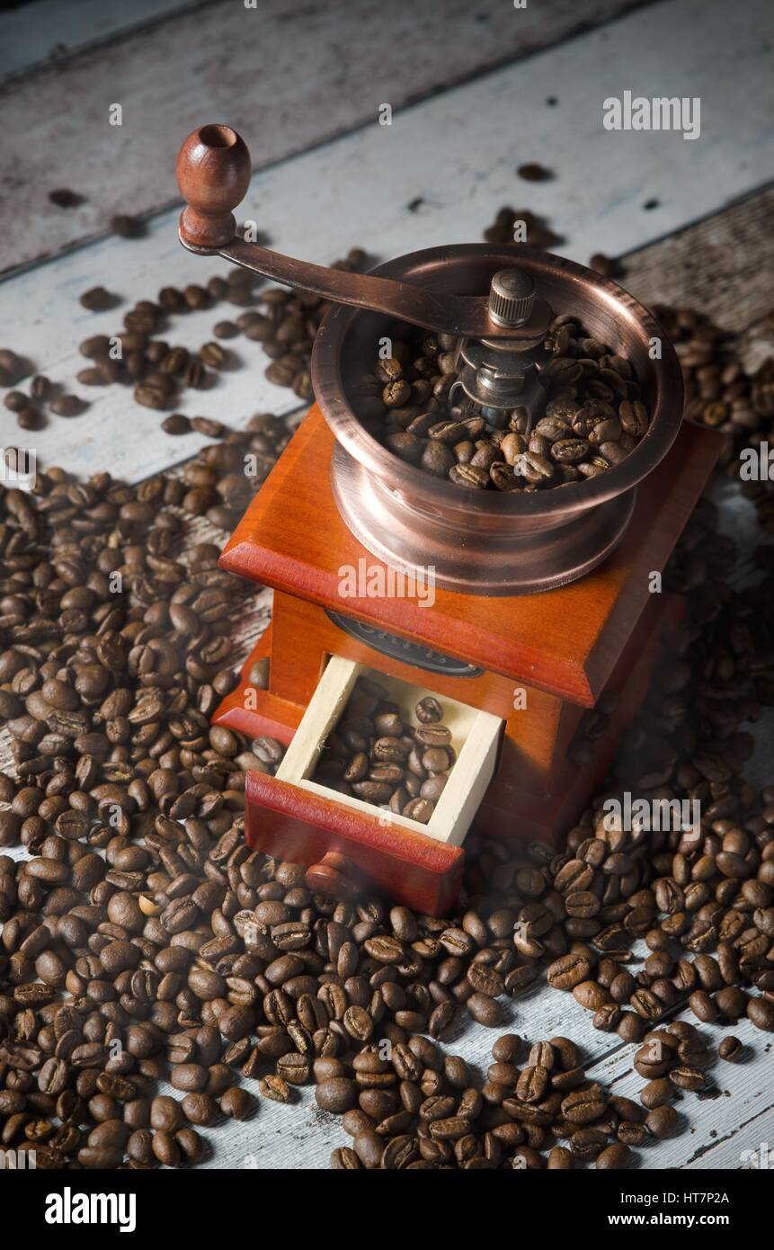 Coffee grinder with roasted beans. Vintage mill composition on wooden background - Stock Image