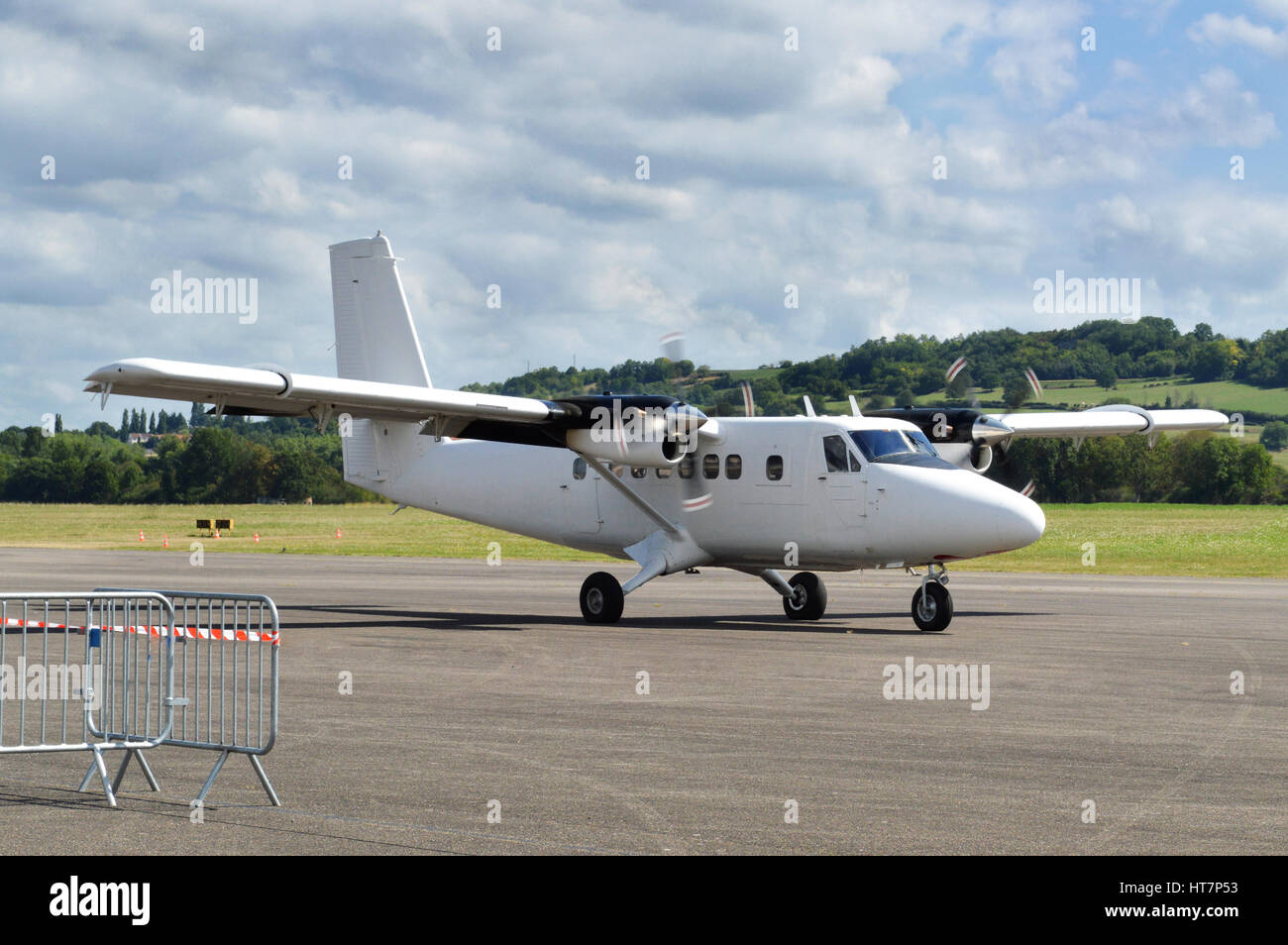 A twin-engine plane taxiing on an airport. - Stock Image