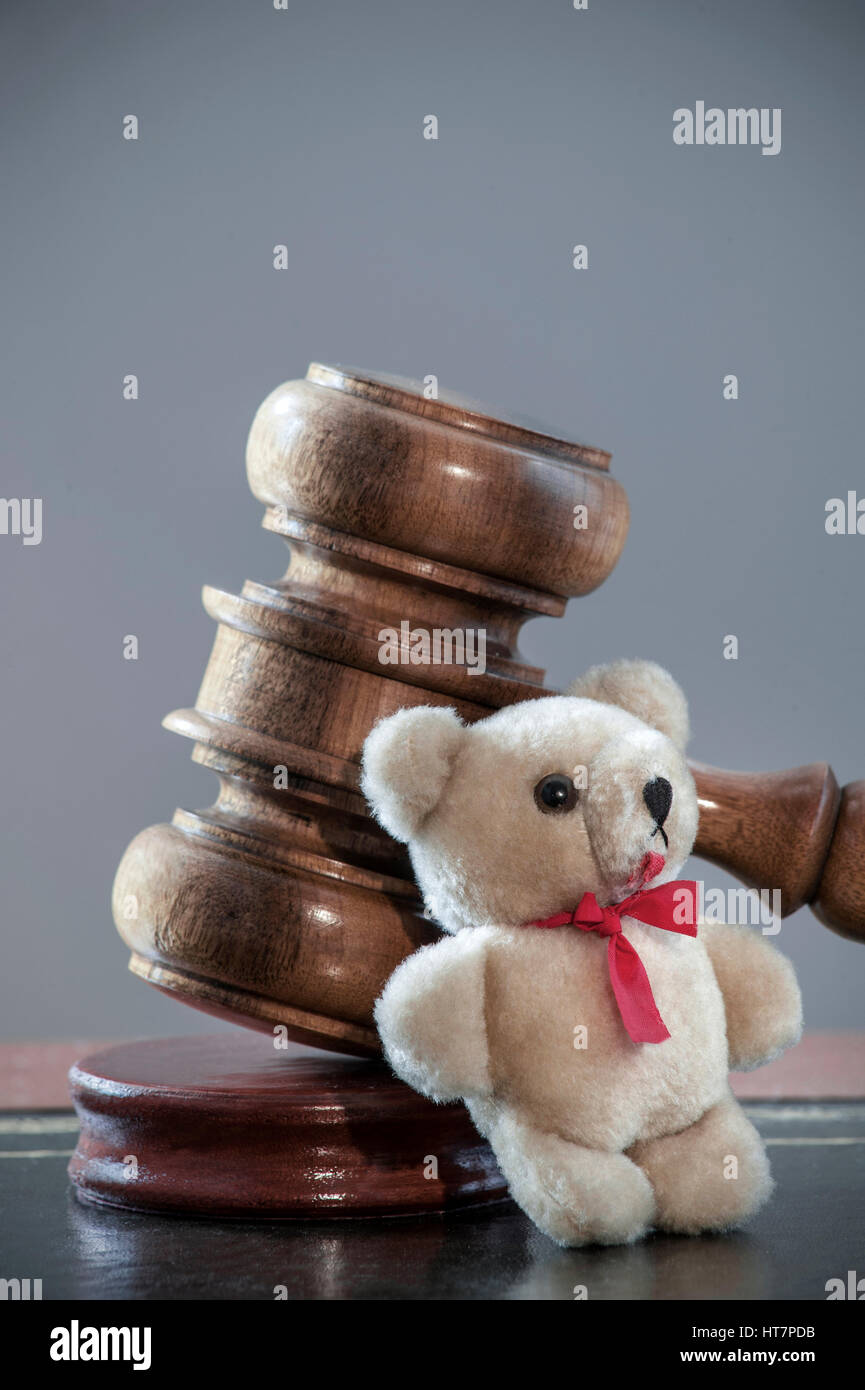 Judges Gavel child protection legal custody abuse etc concept on desk with child's small Teddy Bear leaning - Stock Image