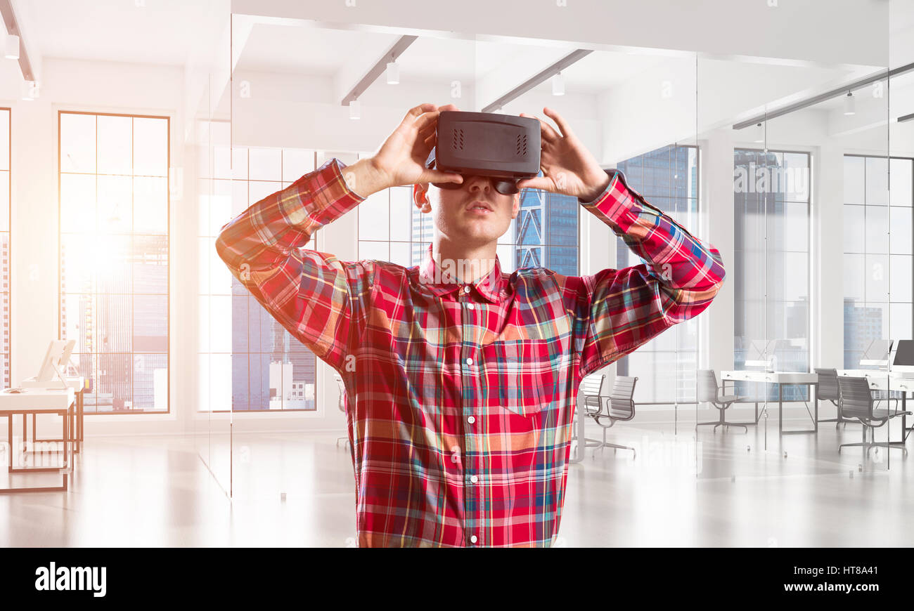 Concept of modern entertaining technologies with man wearing virtual reality mask - Stock Image
