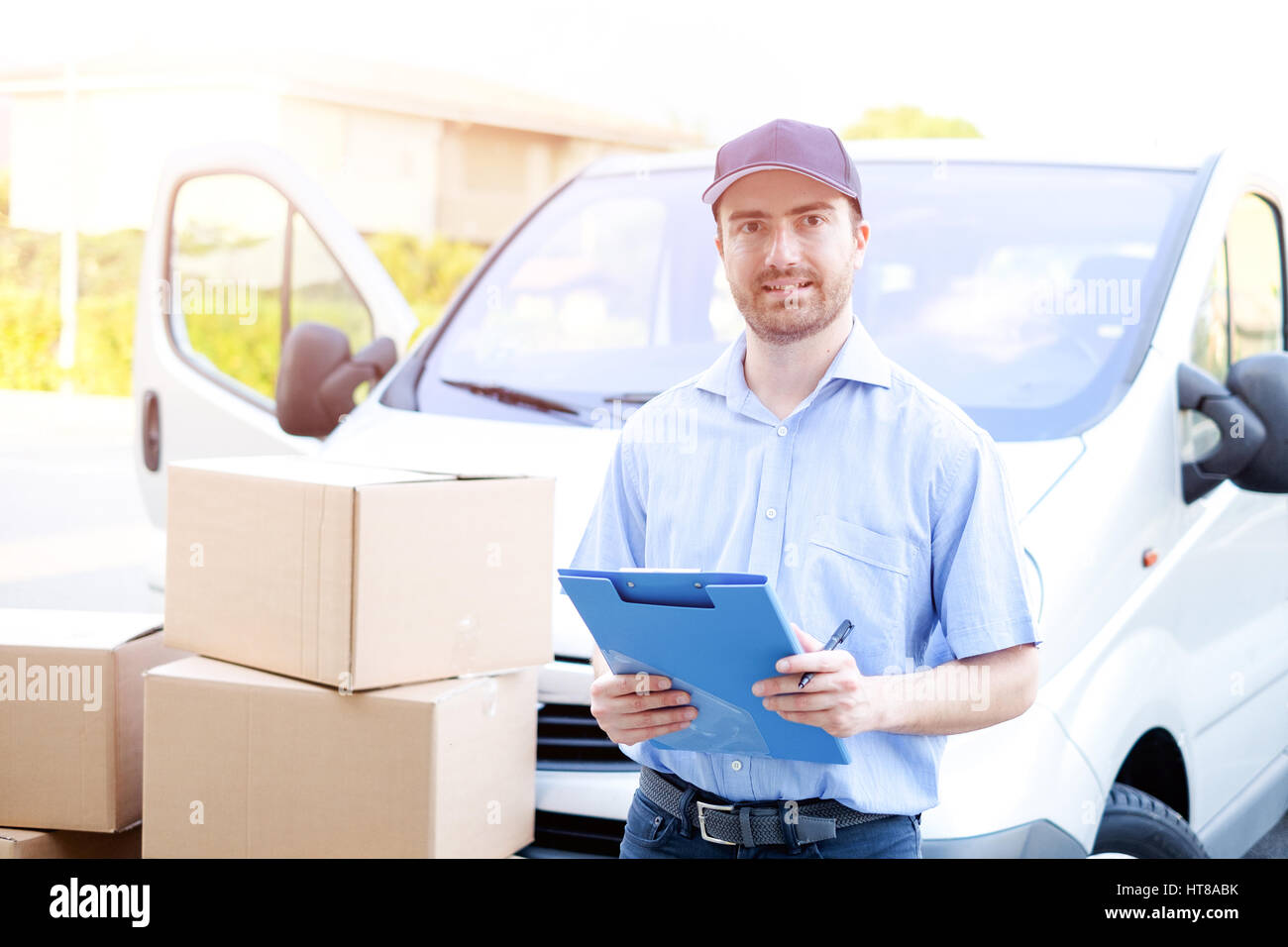 Portrait of confidence express courier next to his delivery van - Stock Image