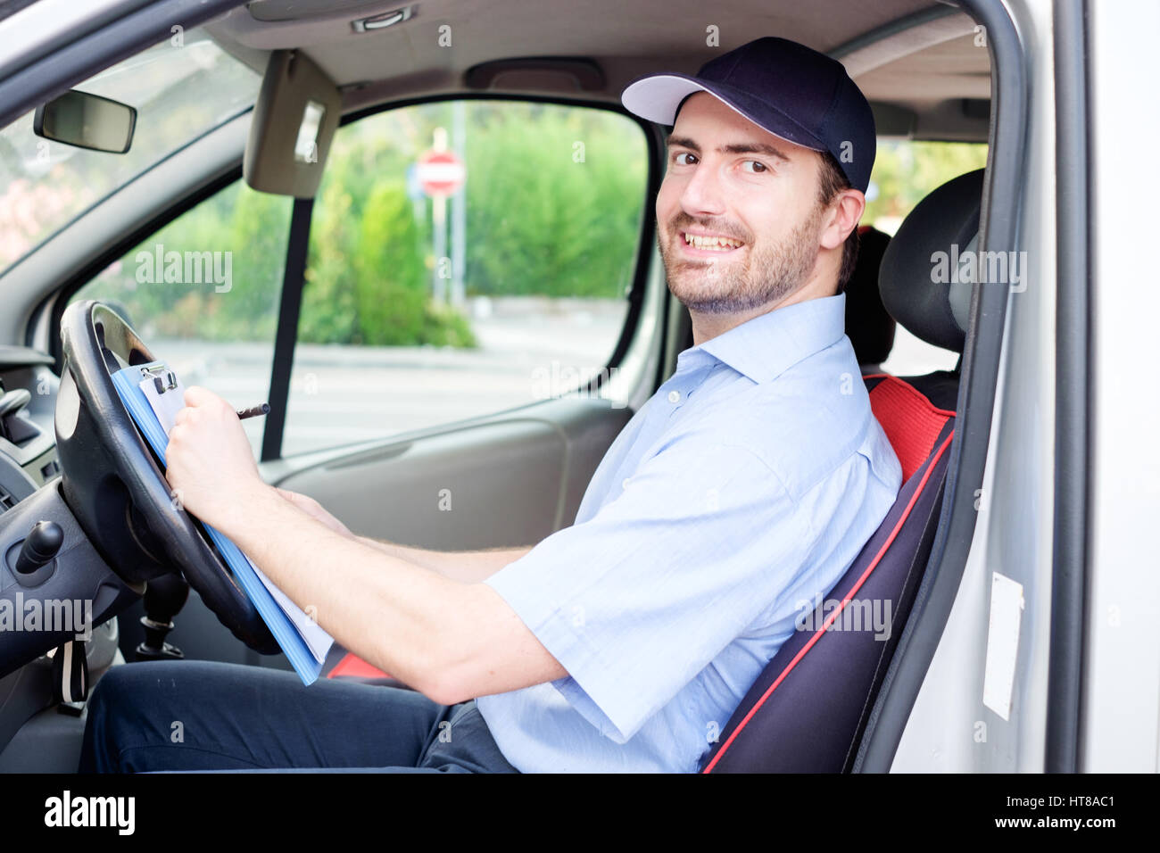 Portrait of confidence express courier on his delivery van - Stock Image