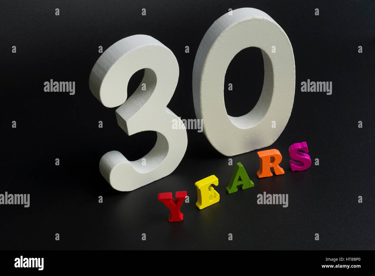 Thirty years of large white numerals on a black background. Stock Photo