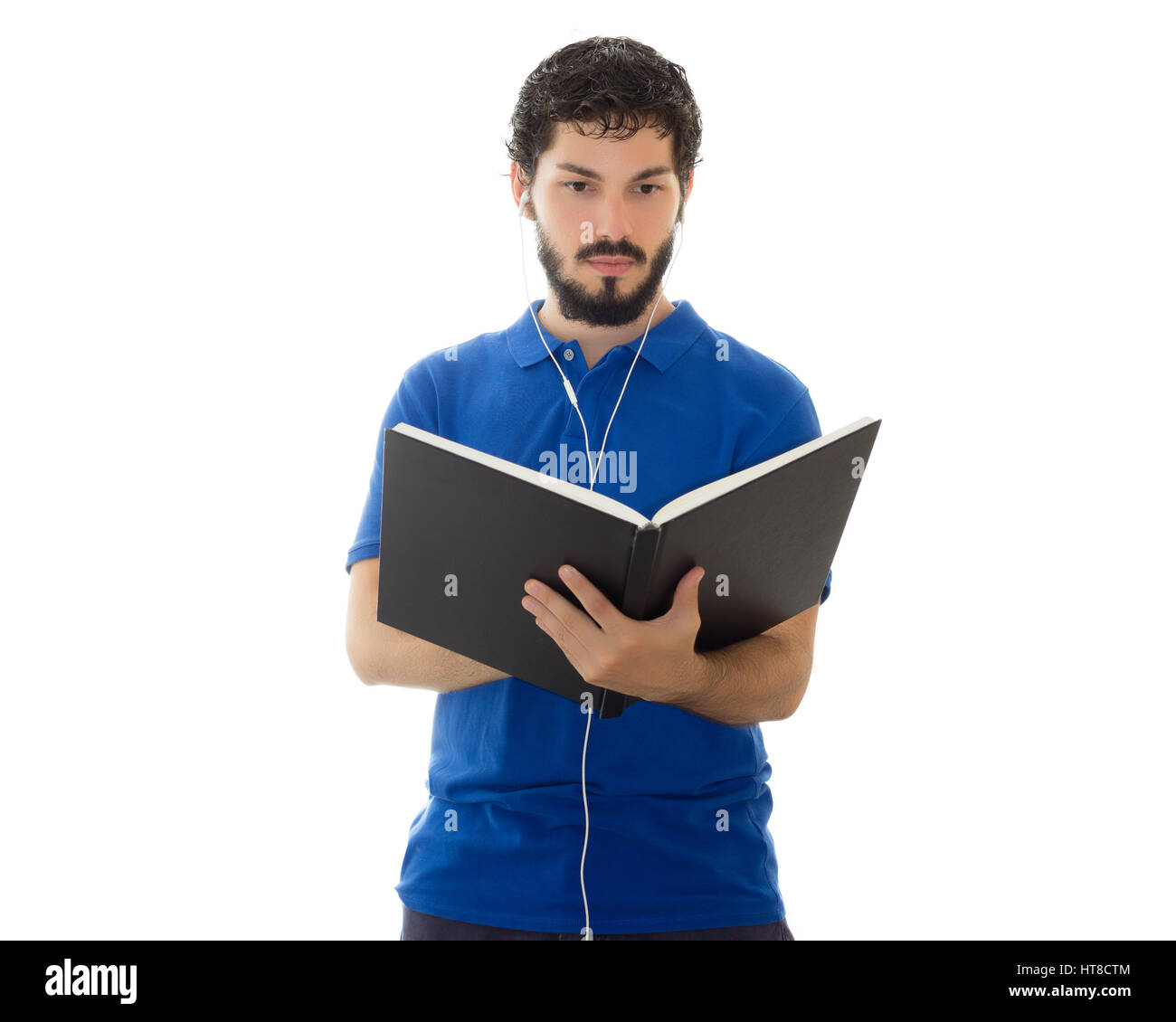 Young scholar checks notes in his notebook and hears music on the headset. Young man wearing blue polo shirt, white - Stock Image