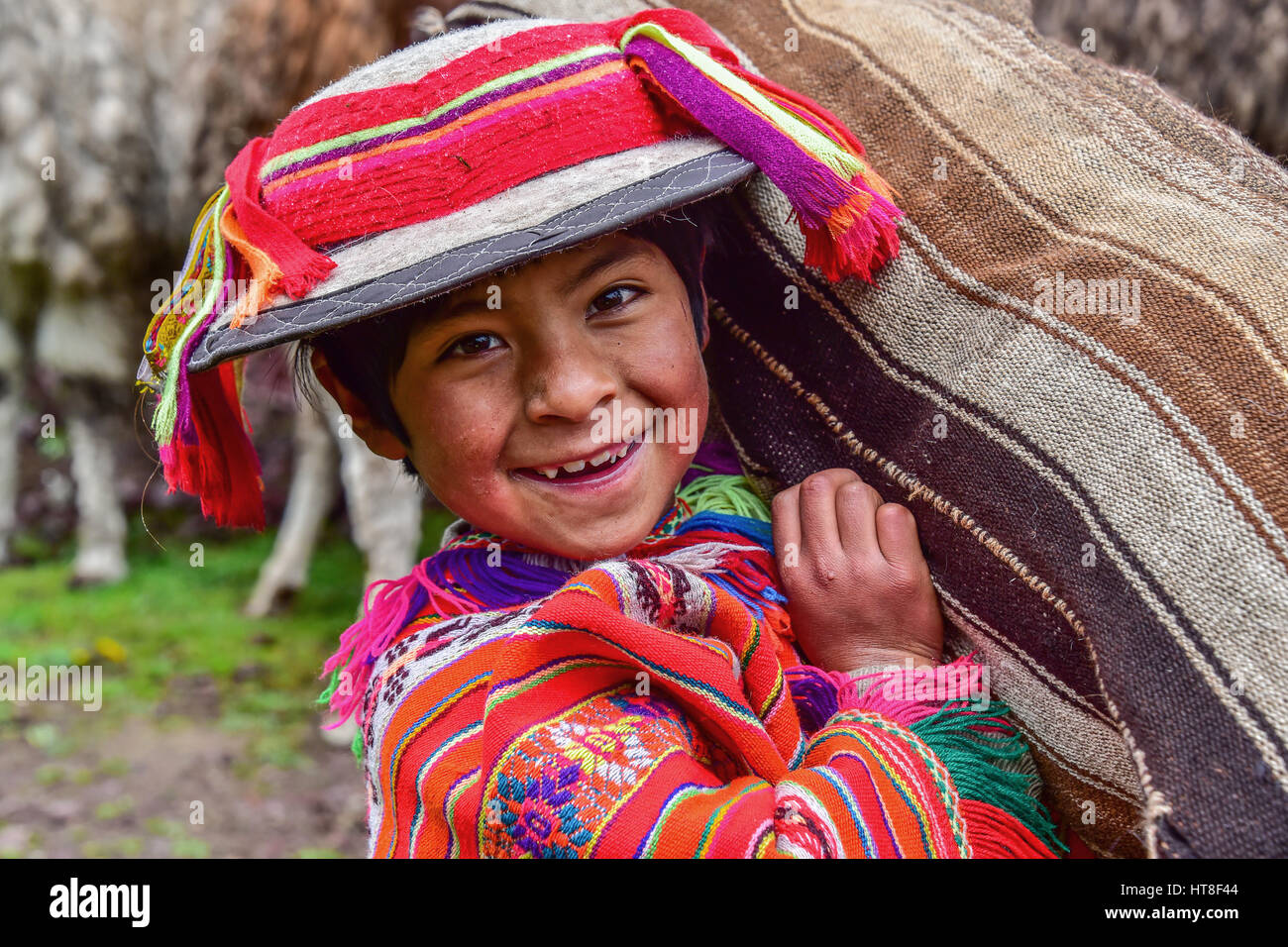 Indio Boy in traditional costume with poncho and hat, carrying bag, near Cusco, Andes, Peru - Stock Image
