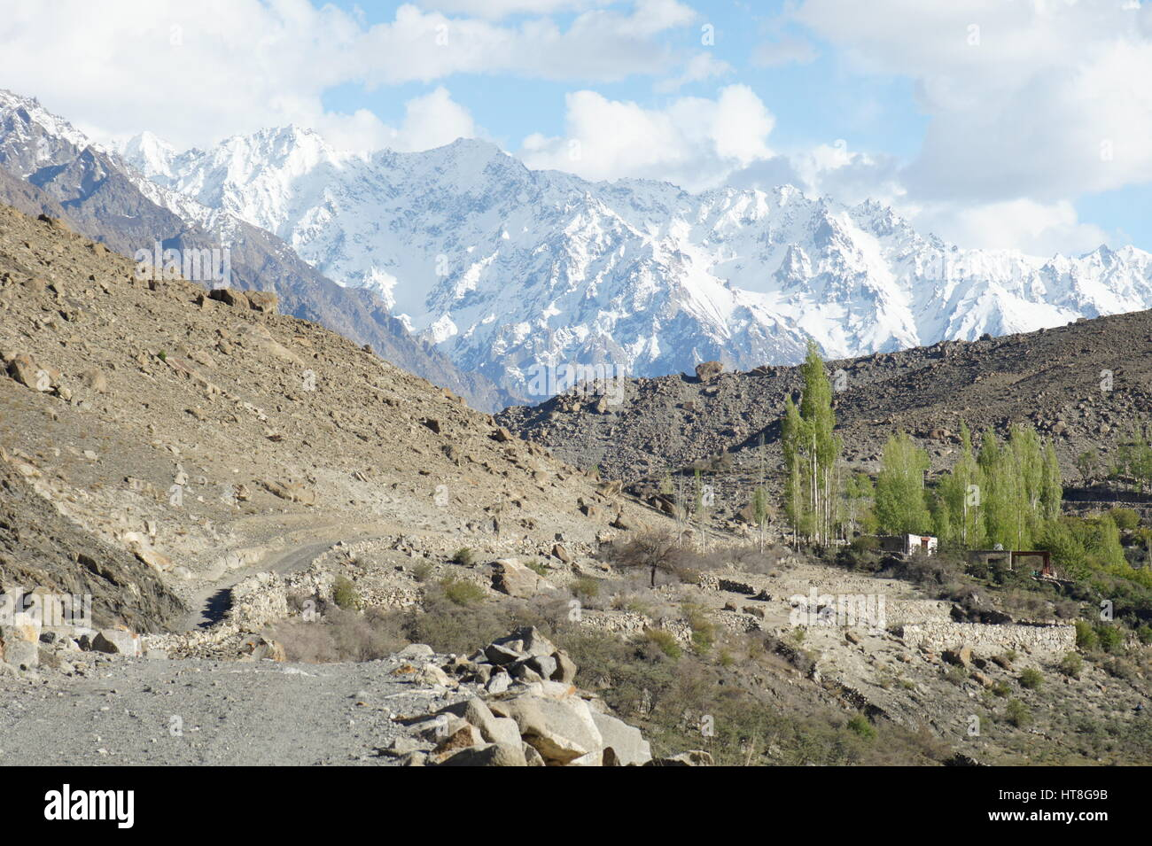 A view of Borit Lake and campsite surrounded by snow covered mountains in Pakistan. Stock Photo