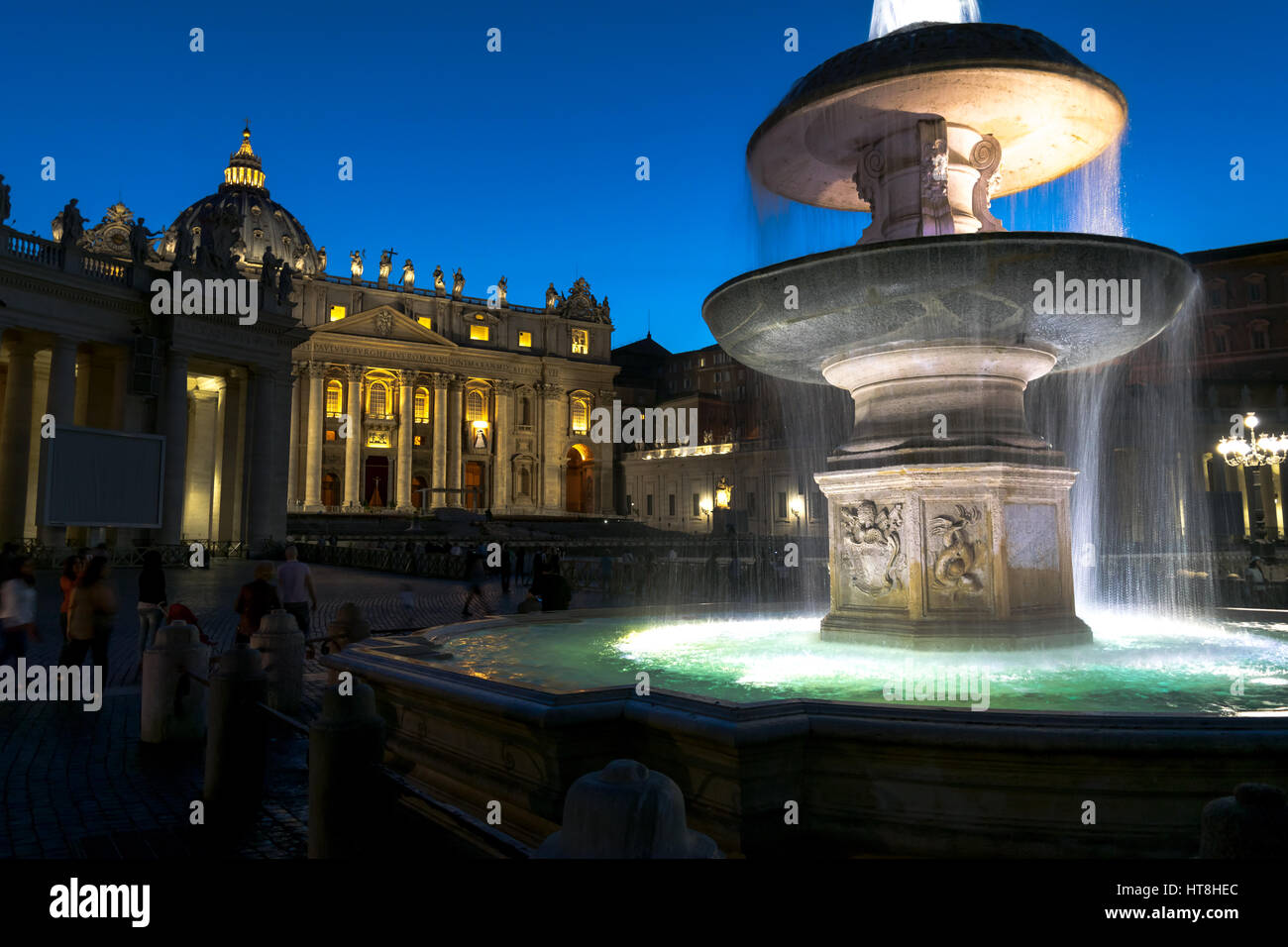 Piazza San Pietro glimmering during the evening hours, with a grandiose water fountain in the foreground. - Stock Image