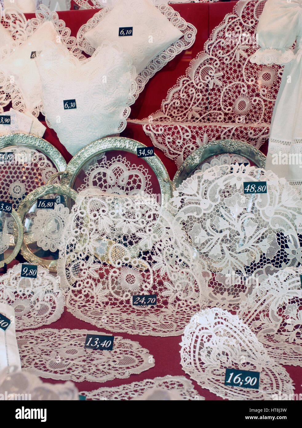 Lace products displayed for sale in a shop window, Bruges, Belgium. - Stock Image