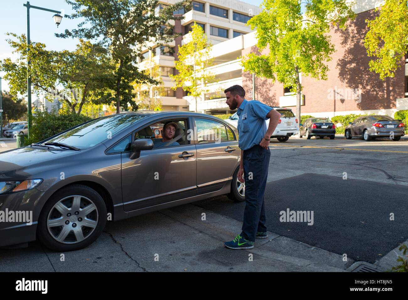 A Honda automobile service adviser speaks with a driver as he pulls