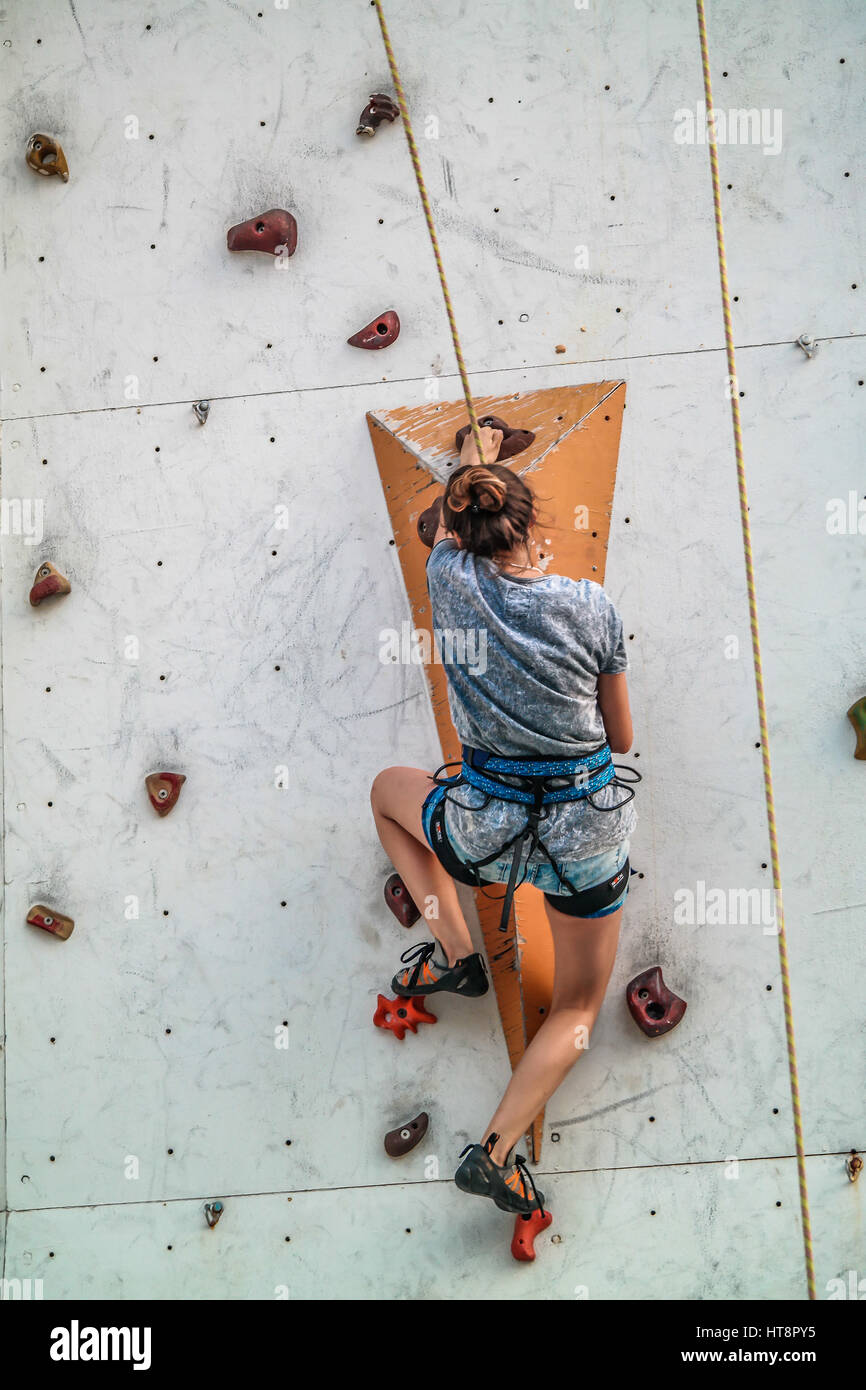 girl with skills climbing to boulder wall. - Stock Image