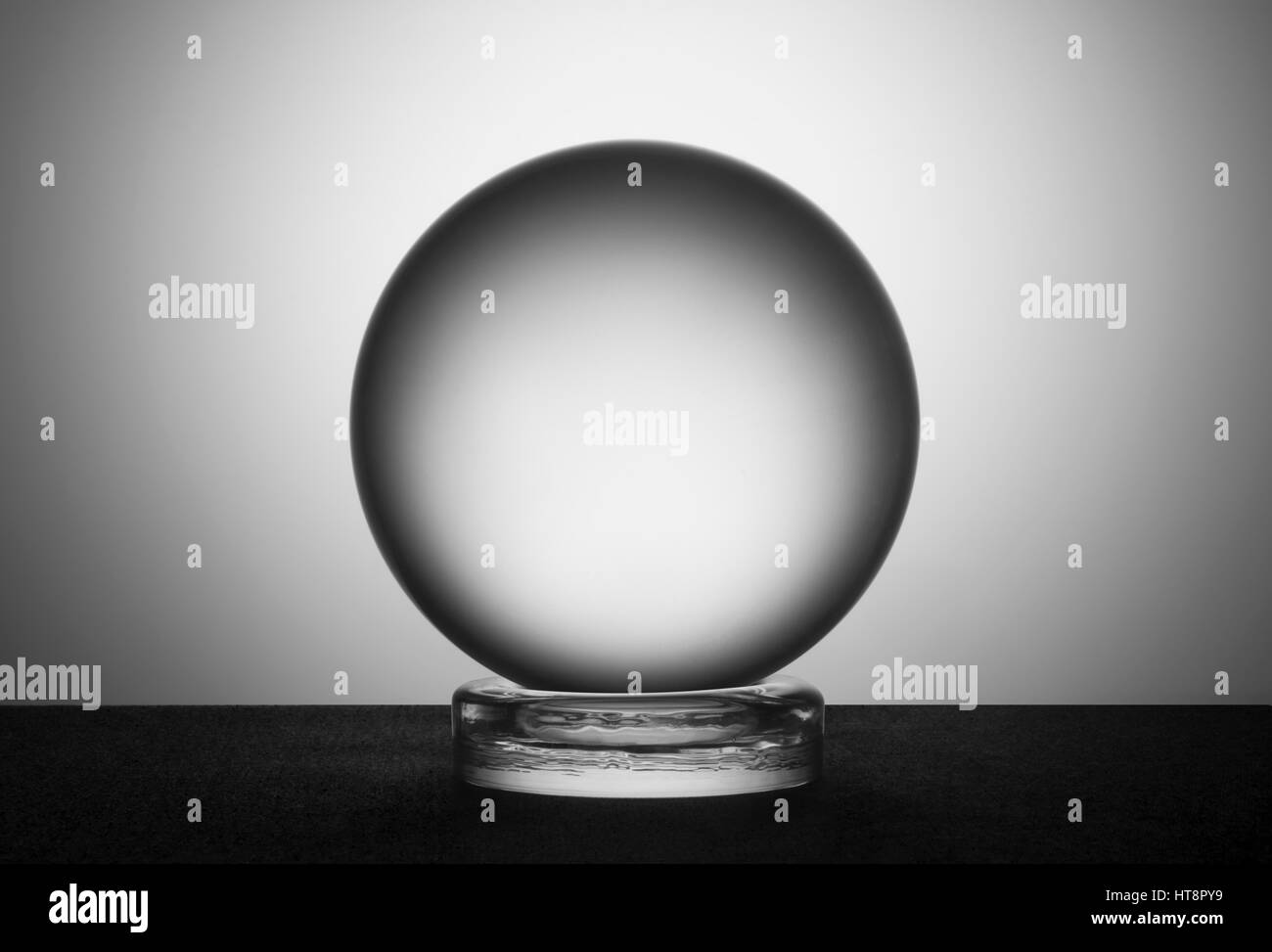 A large crystal ball against a plain background - Stock Image